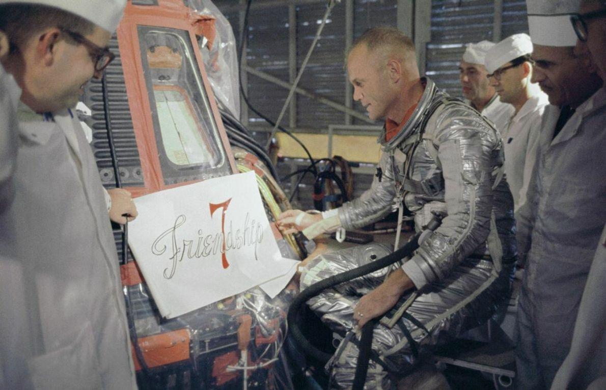 Astronaut John Glenn betrachtet das Logo für die Friendship 7, das auf die Außenseite seiner Mercury-Raumkapsel ...