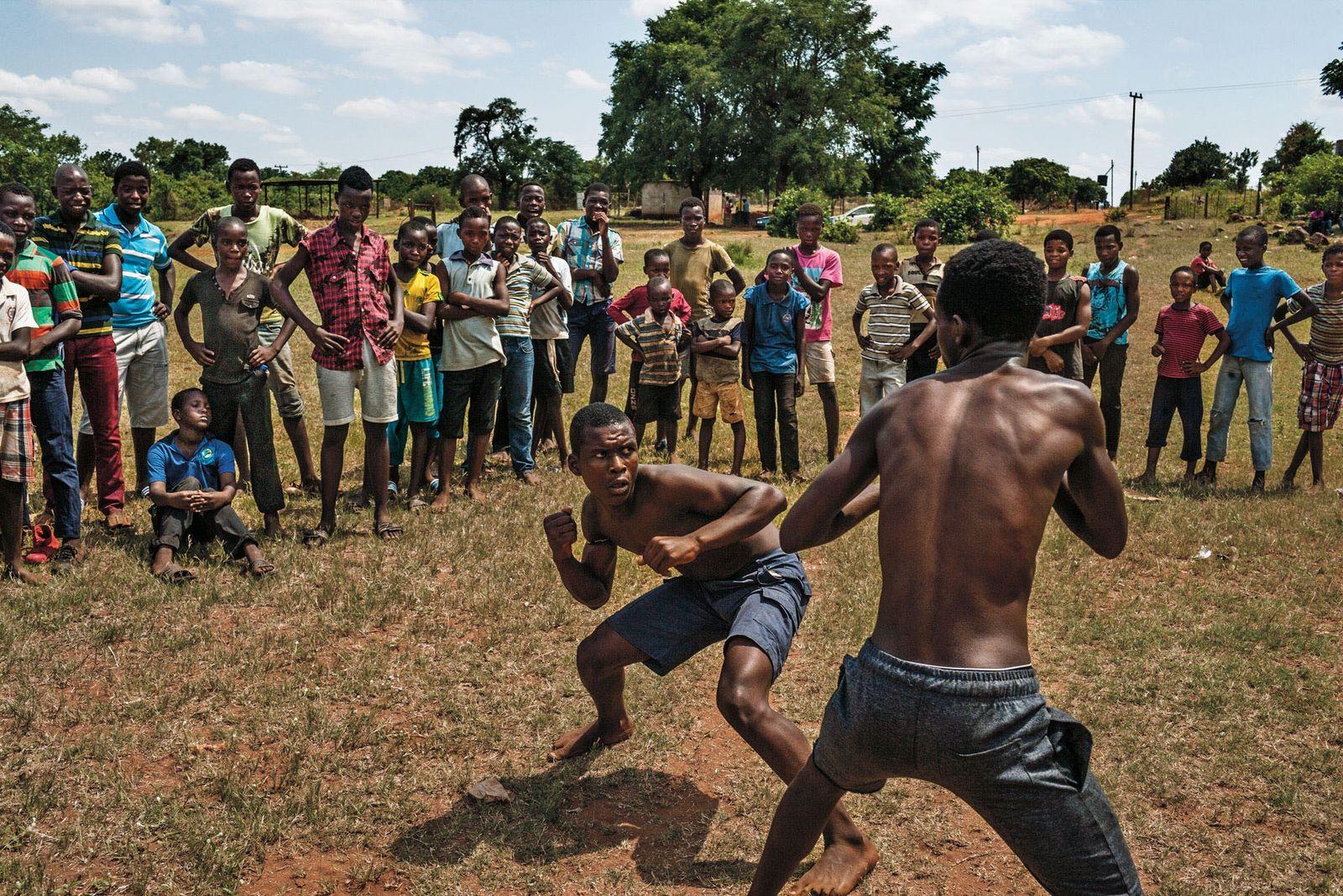 Mit bloßen Fäusten und bereit zum Zuschlagen pflegen Jungen vom Stamm der Venda in Tshifudi, Südafrika, ...