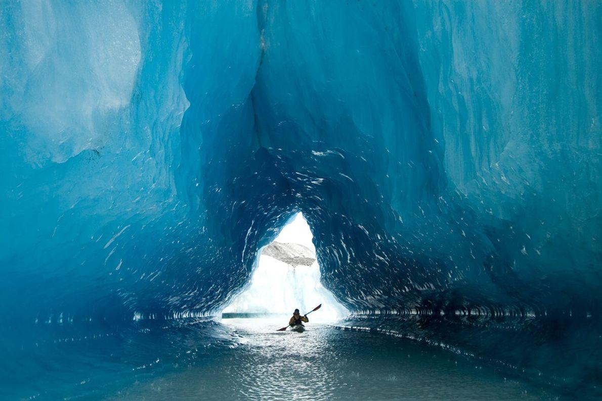 Ein Kajakfahrer durchquert eine Gletscherhöhle in der Resurrection Bay in der Nähe der Stadt Seward in ...