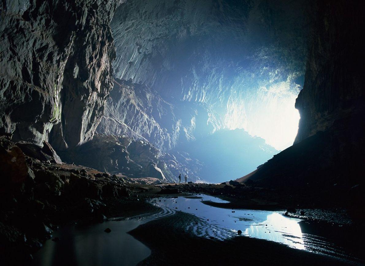 Zwei Menschen blicken zum Eingang der Deer Cave im Mulu-Nationalpark auf Borneo. Das Duo befindet sich ...