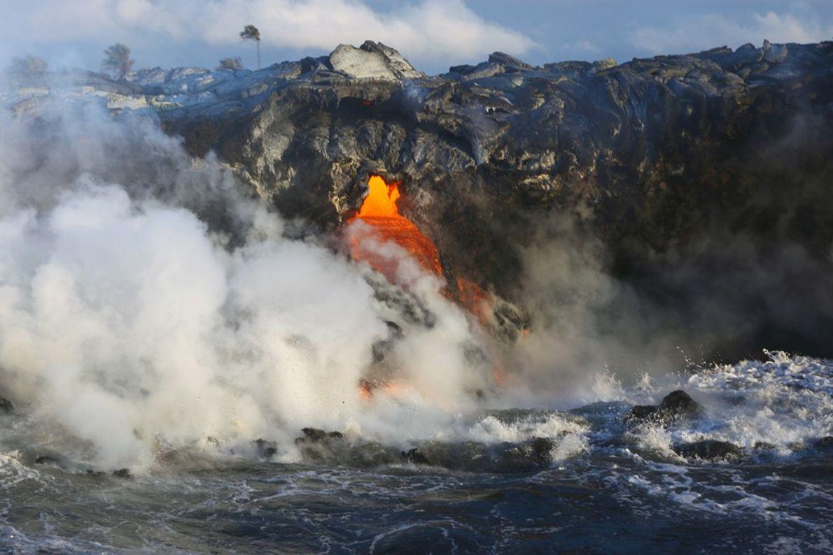 Dampf steigt aus dem Pazifik auf, während sich flüssige Lava aus dem Kīlauea in das Meer ...