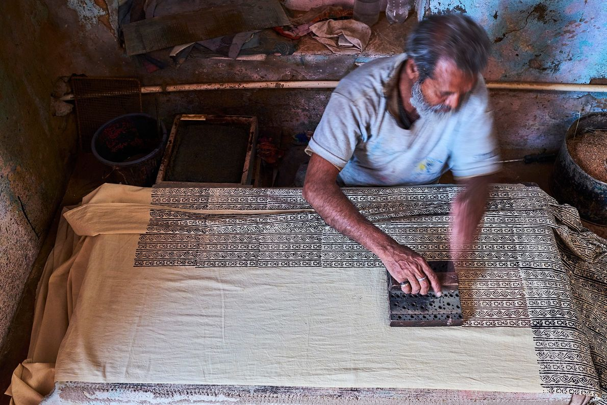 A craftsman uses a wooden block to print sari fabric in Rajasthan, India. The region is ...