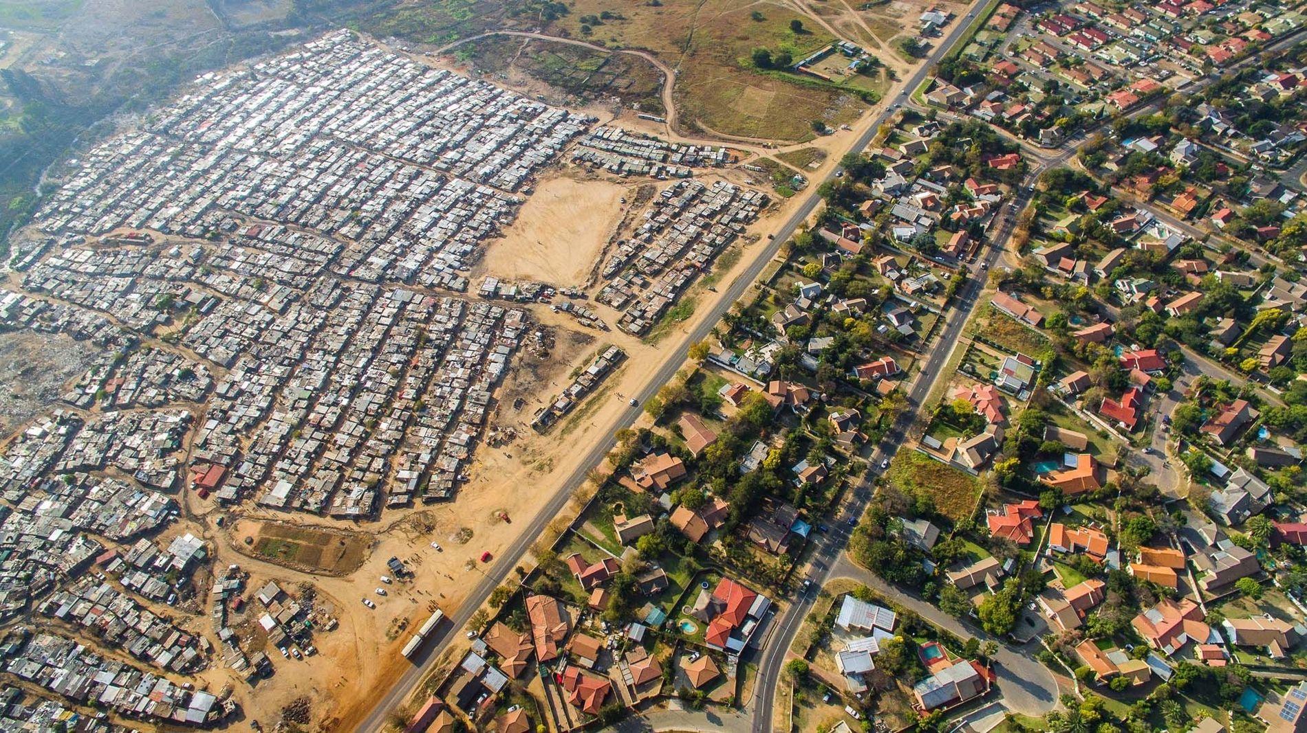 In Boubosrand, einem Vorwort im Nordwesten von Johannesburg in Südafrika, grenzt ein Viertel mit strahlend blauen Swimmingpools und grünen Rasenflächen an einen Slum voller Wellblechhütten.