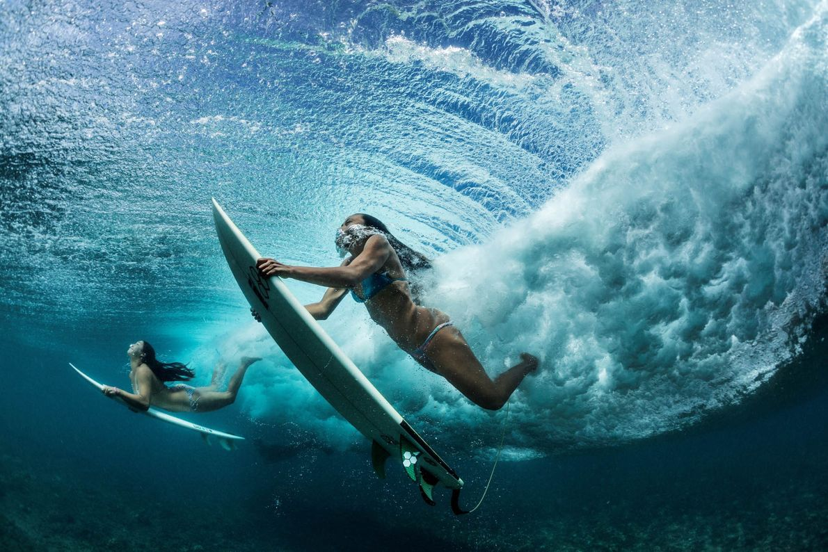Surferinnen tauchen unter eine Welle