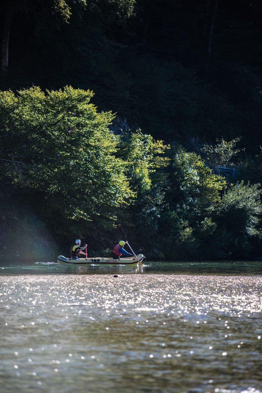 Auf einem ruhigeren Abschnitt der Soča gleiten zwei Rafter über das klare Wasser.