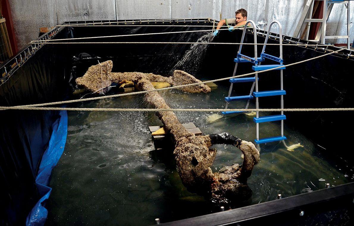 Ein Restaurator sprüht Wasser auf einen Anker der Queen Anne's Revenge, um ihn feucht zu halten, ...