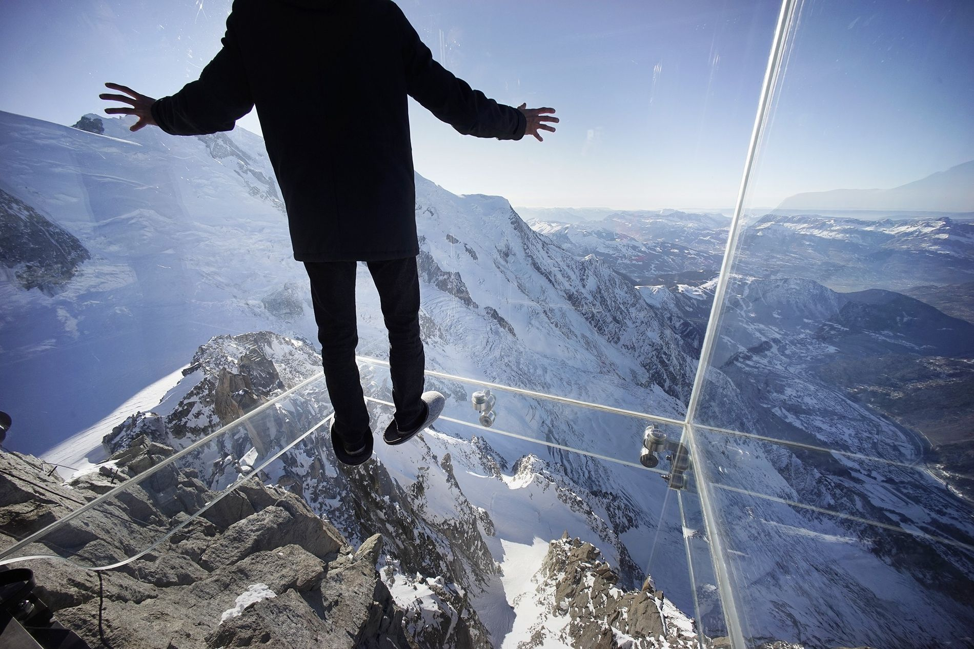 Ein Journalist steht im Glaskubus über den französischen Alpen.