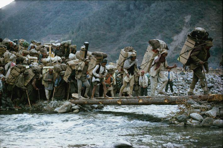 Mehr als 900 Träger überqueren eine Baumstammbrücke auf ihrem 300 Kilometer langen Fußmarsch zum Mount Everest. ...