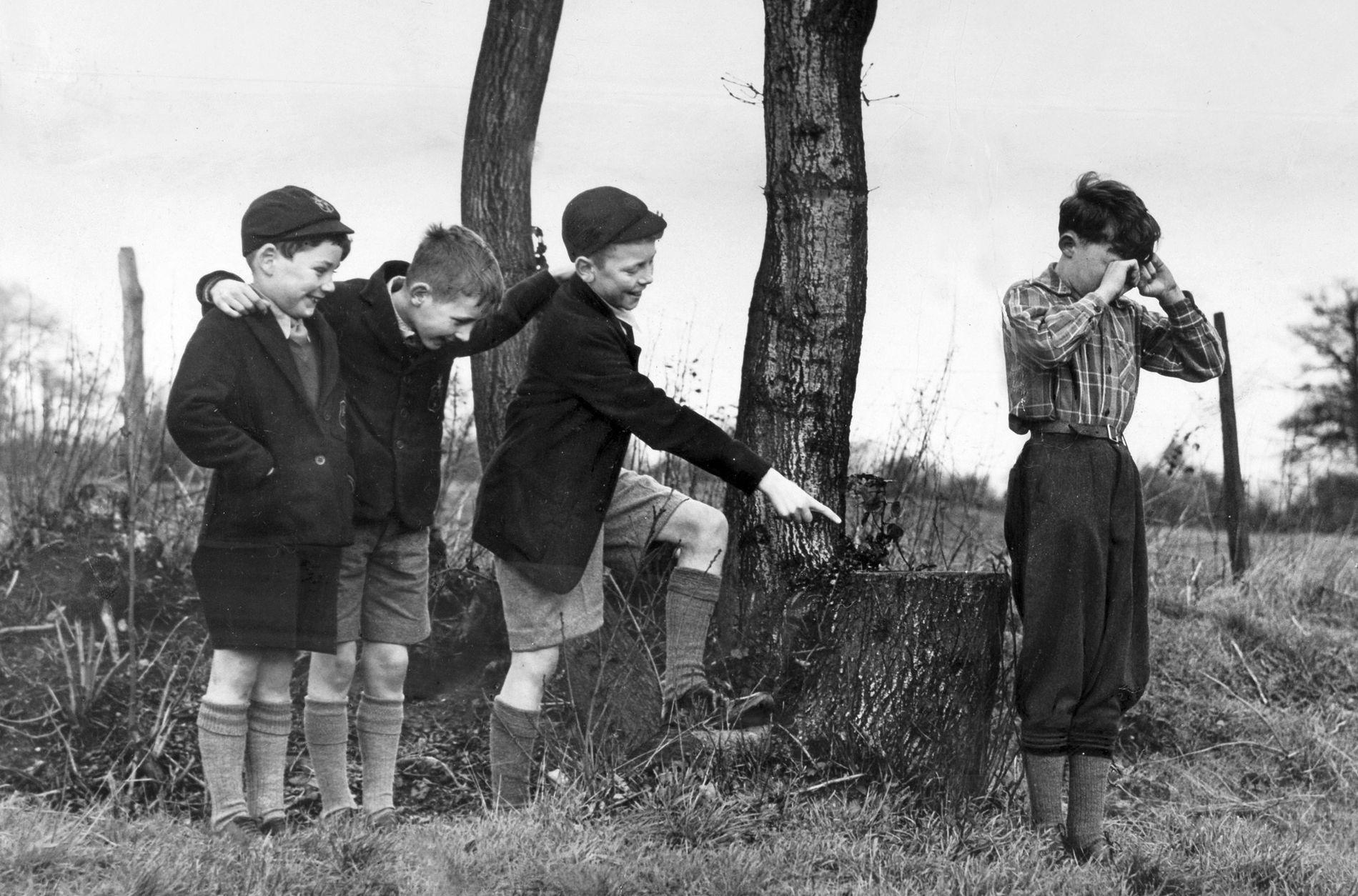 In diesem Foto aus den 1940ern machen sich drei Jungen über die Kleidung eines vierten Jungen ...