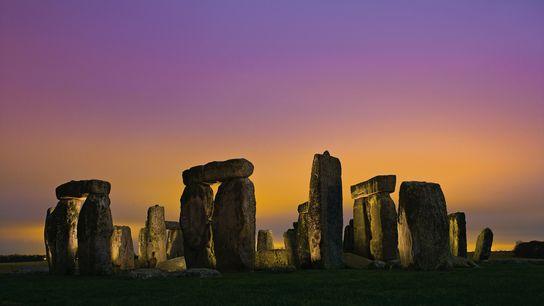 Die Lichter der Stadt Amesbury erleuchten die tiefhängenden Wolken über Stonehenge.
