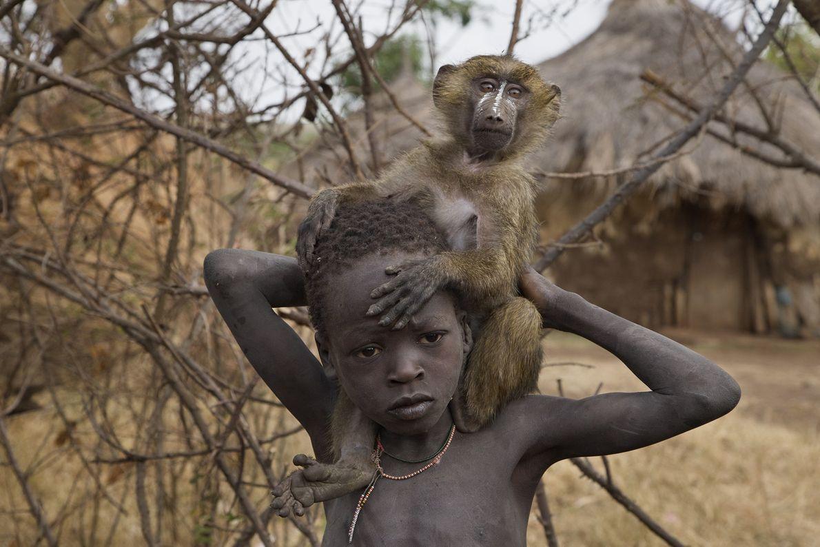 Ein äthiopischer Junge und sein zahmer Pavian leisten sich im Suri-Dorf Tulgit gegenseitig Gesellschaft.
