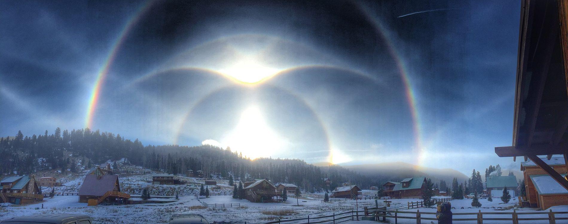 Halos, Lichtbögen und Lichtsäulen wurden 2015 über einem verschneiten Bergkamm in Red River, New Mexico, USA ...