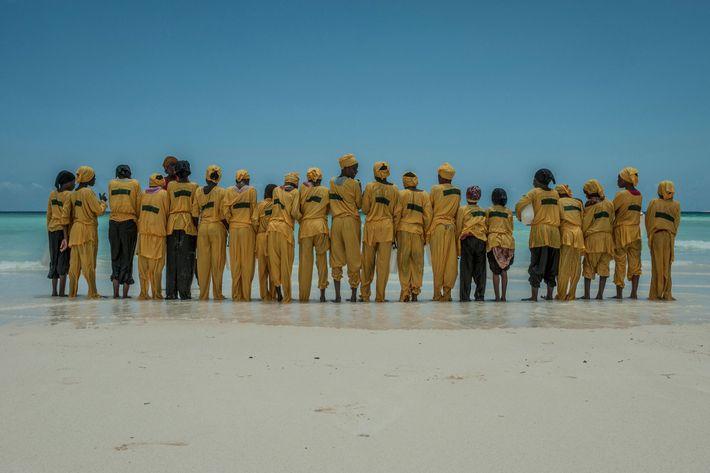 Schülerinnen in einer Reihe am Strand