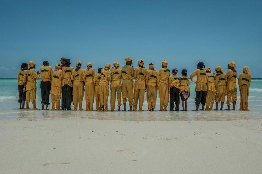 Schülerinnen bilden am Strand von Mnyuni auf Unguja eine Reihe, nachdem sie gelernt haben, wie man ...