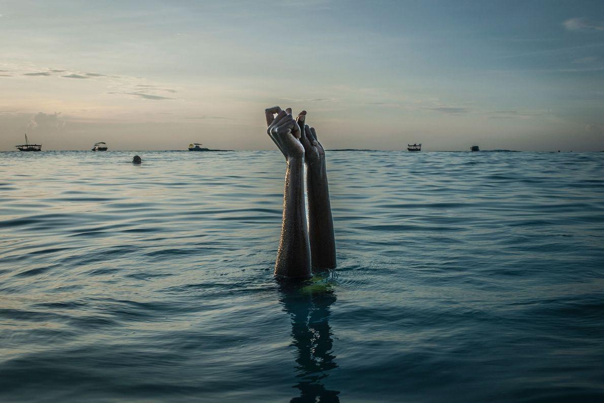 Hände, die aus dem Wasser ragen