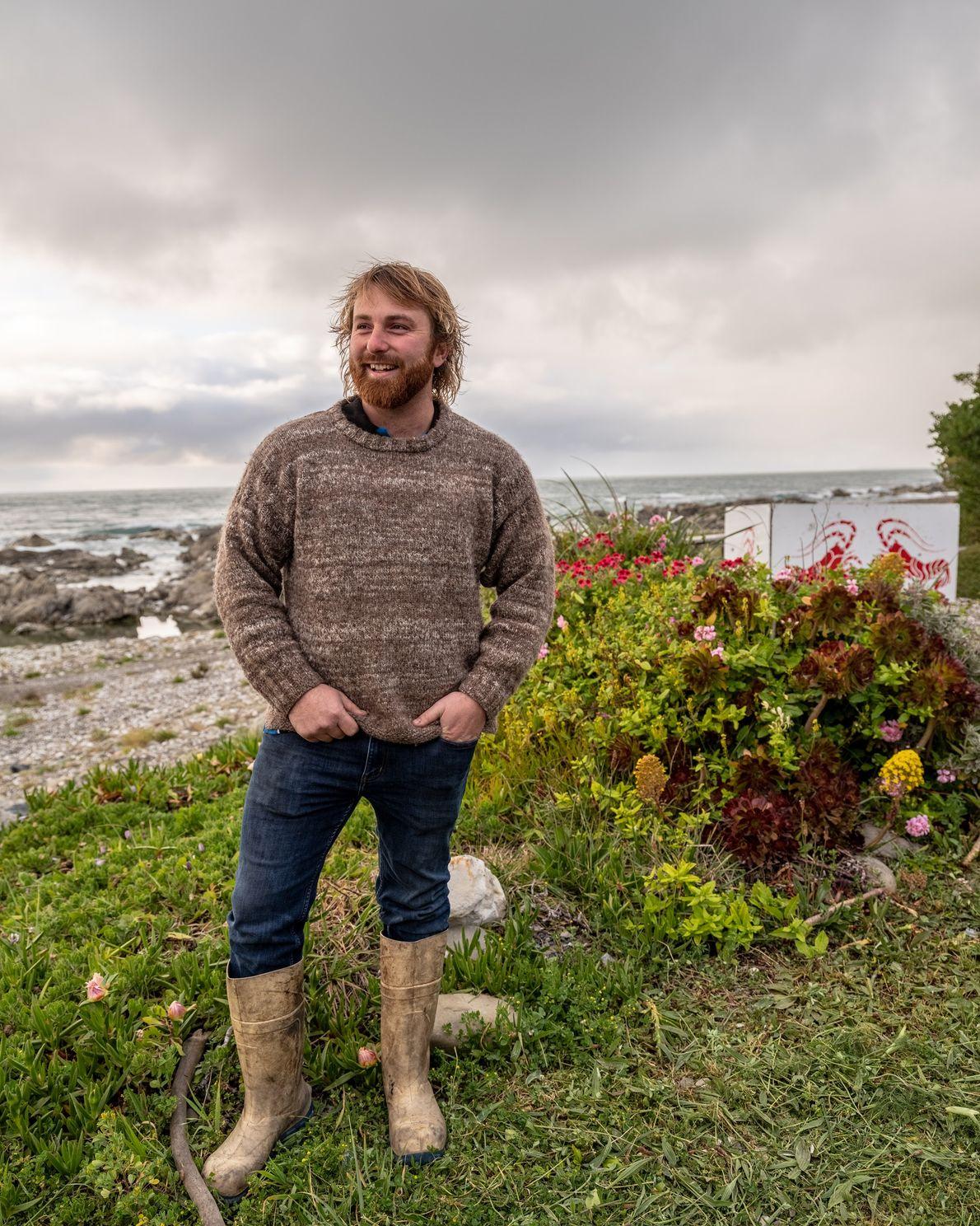 Johnny Clark, der Eigentümer von Nin's Bin, trägt die übliche Kleidung der Einheimischen: Pullover, Jeans, ...