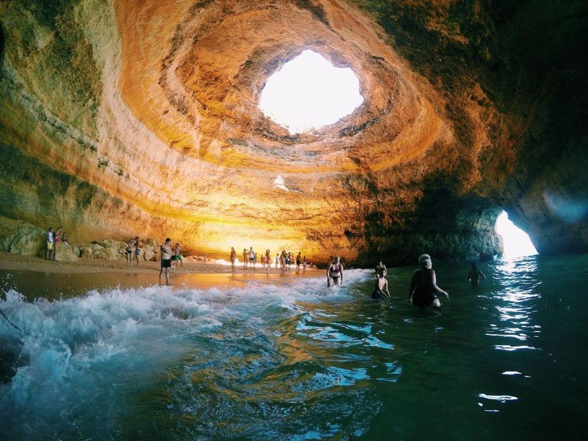 Badegäste vergnügen sich an diesem außergewöhnlichen Strand in einer Höhle.