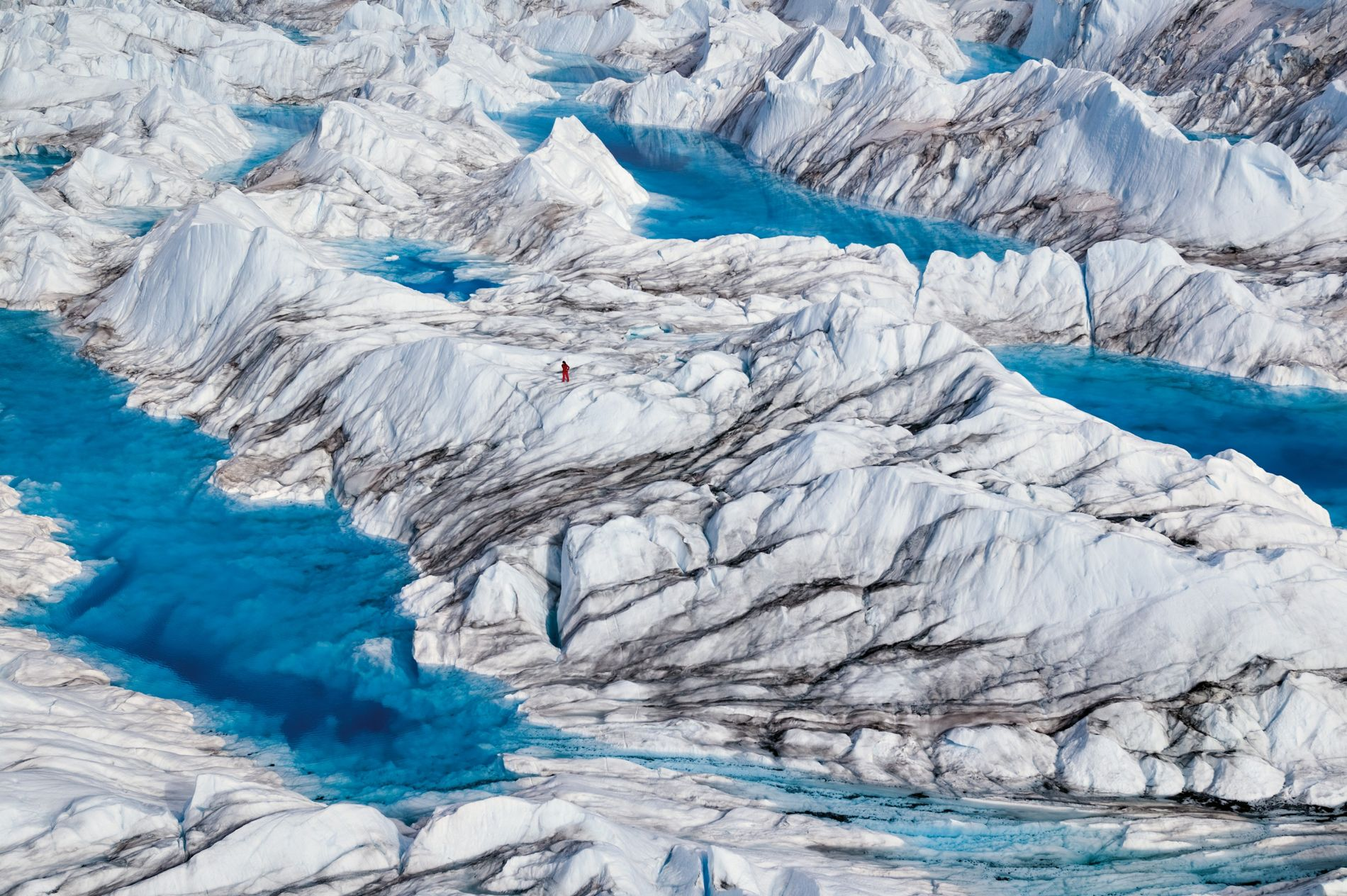 Ein Wissenschaftler in rotem Overall untersucht Schmelzwasserseen auf dem Grönländischen Eisschild. Seit 2002 gingen hier jährlich im Schnitt 287 Milliarden Tonnen Eis verloren