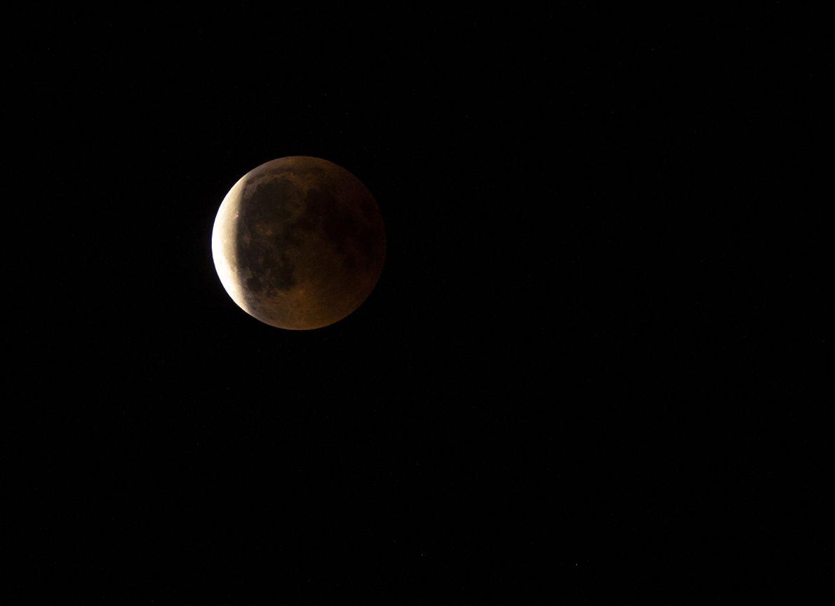 Der Kernschatten der Erde bedeckt den Mond nicht mehr vollständig und das tiefe Rot, in dem ...
