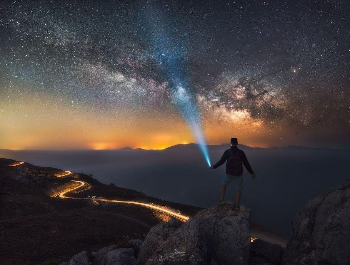 Der Schein der Taschenlampe scheint durch die leuchtende Milchstraße am Nachthimmel zu brechen.