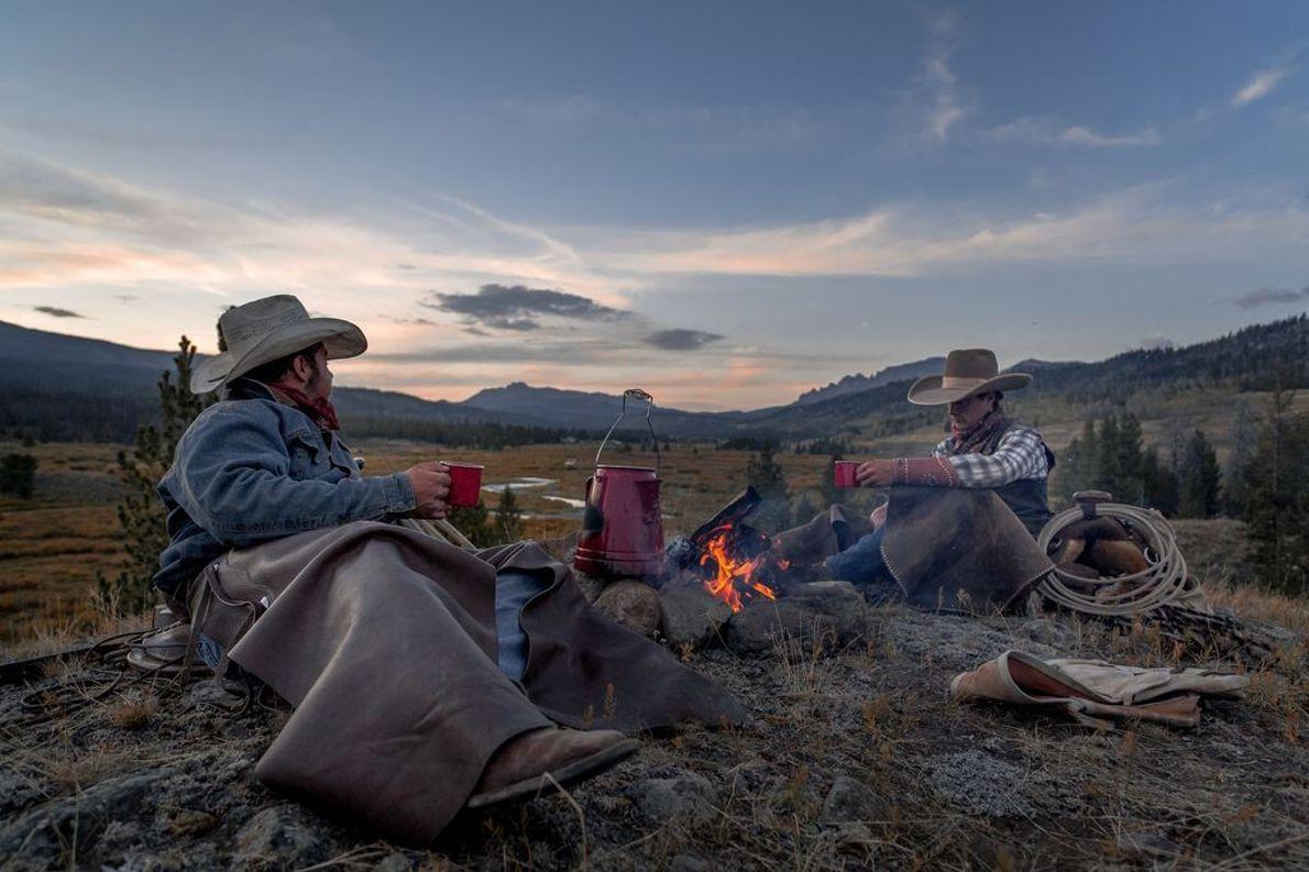 Die Cowboys Randall und Caleb genießen ihren morgendlichen Kaffee in Wyoming. Sie folgen dem Wind River ...