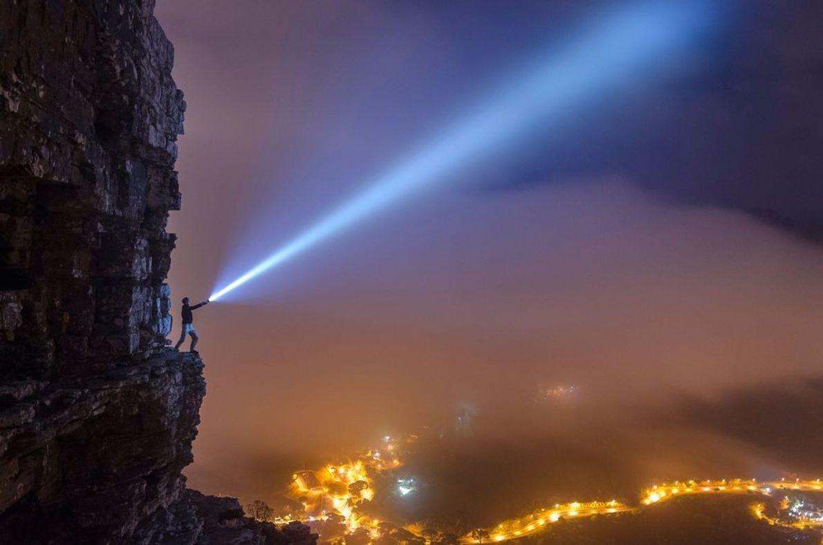 Person strahlt Licht in die Nacht