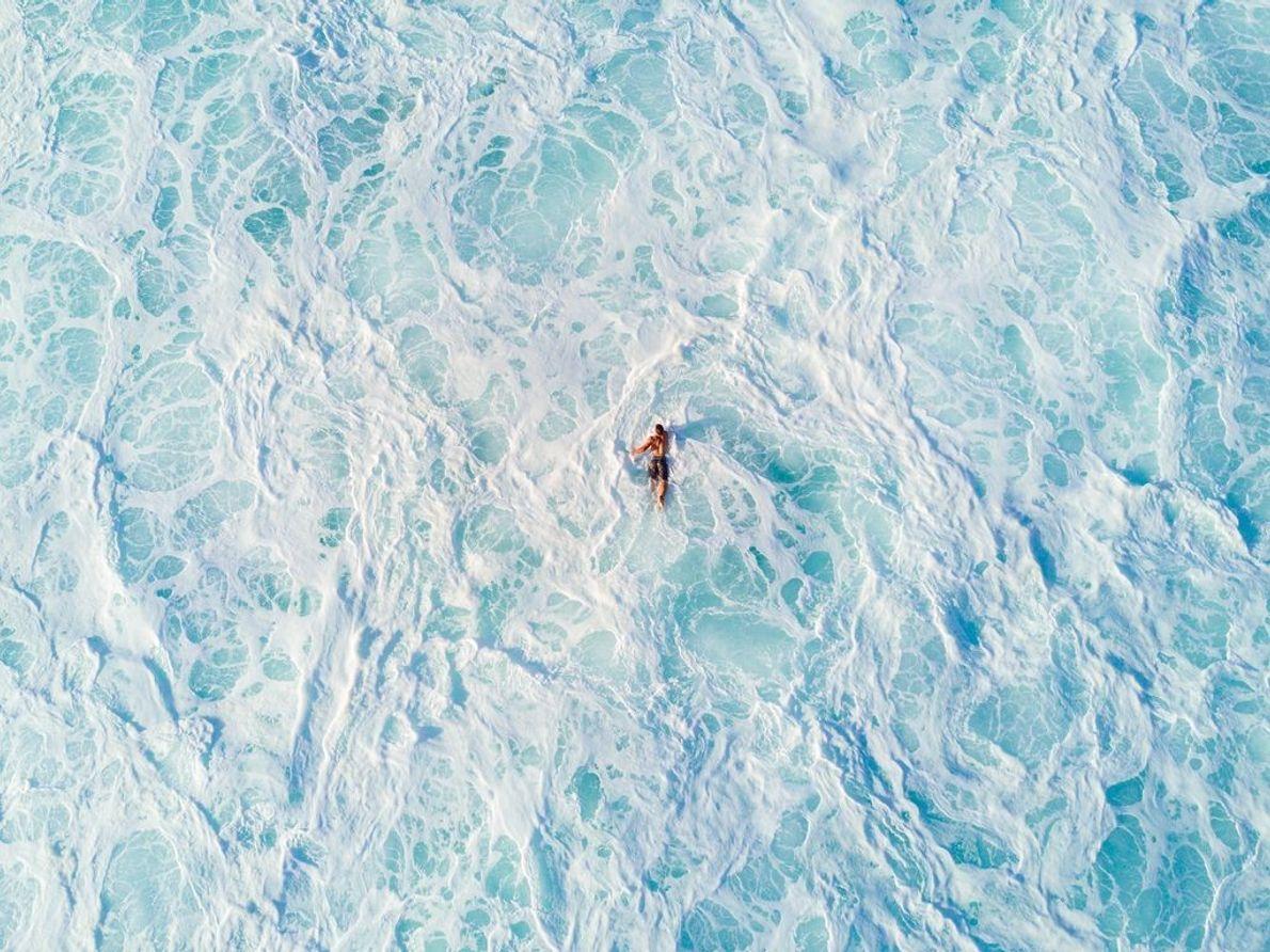 Ein Surfer paddelt auf seinem Board durch das schäumende weiße Wasser, nachdem sich eine Welle gebrochen ...