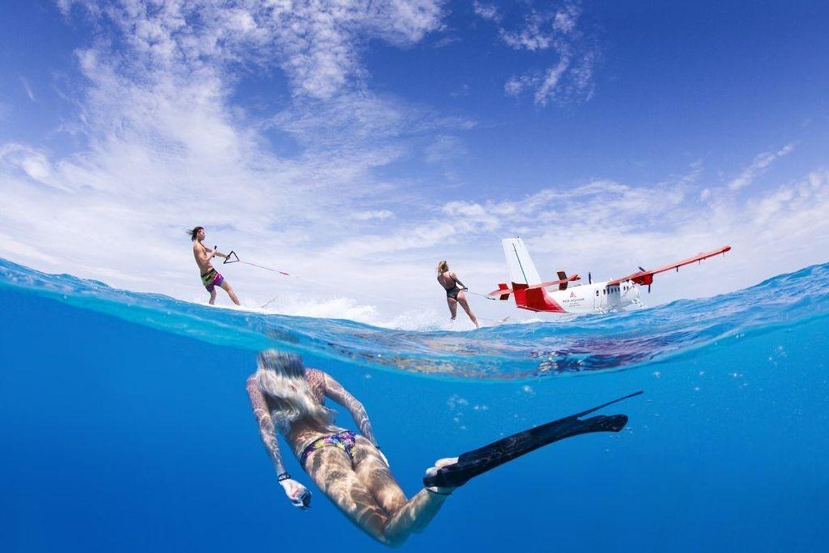 Eine Over-Under-Aufnahme zeigt Menschen beim Schnorcheln und beim Wasserski.