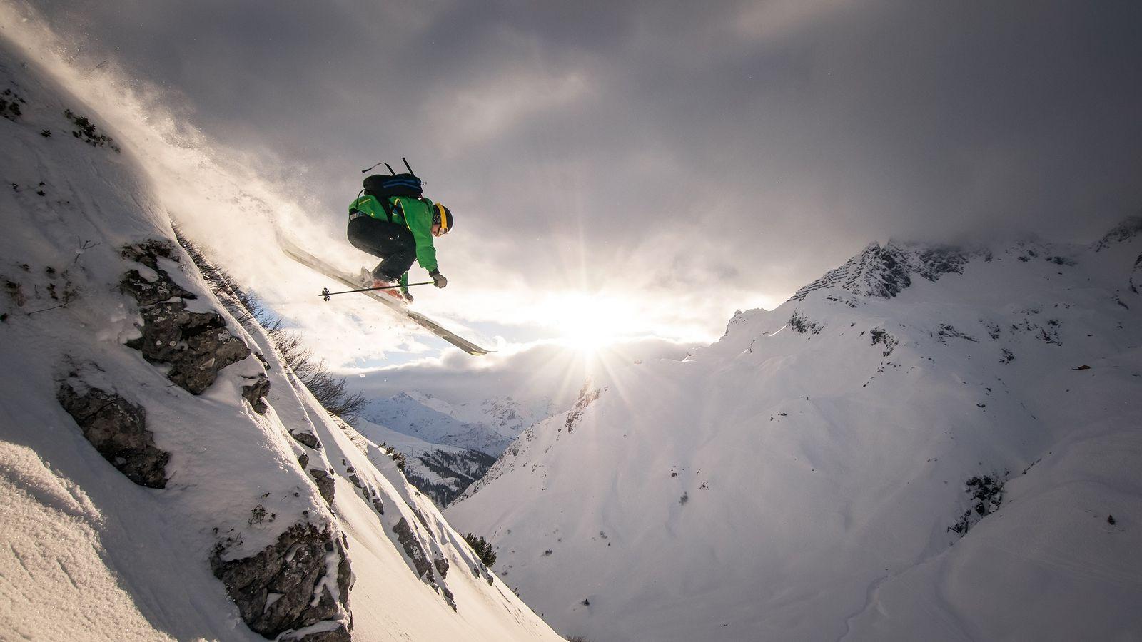 Bewegung in den Alpen: Ein Skifahrer saust bergab und zieht eine Schneefahne hinter sich her.