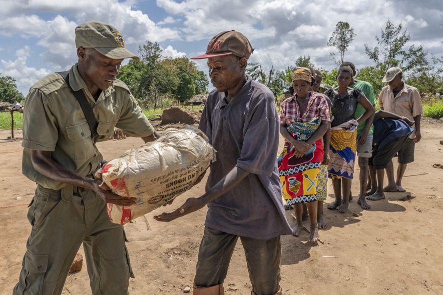 Der Ranger Macane Costa Alberto Jornal verteilt Lebensmittel an die Bewohner der Gemeinde Micheu, die sich ...