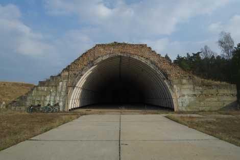 Einer der grasbewachsenen Hangars steht völlig verlassen im Wald.