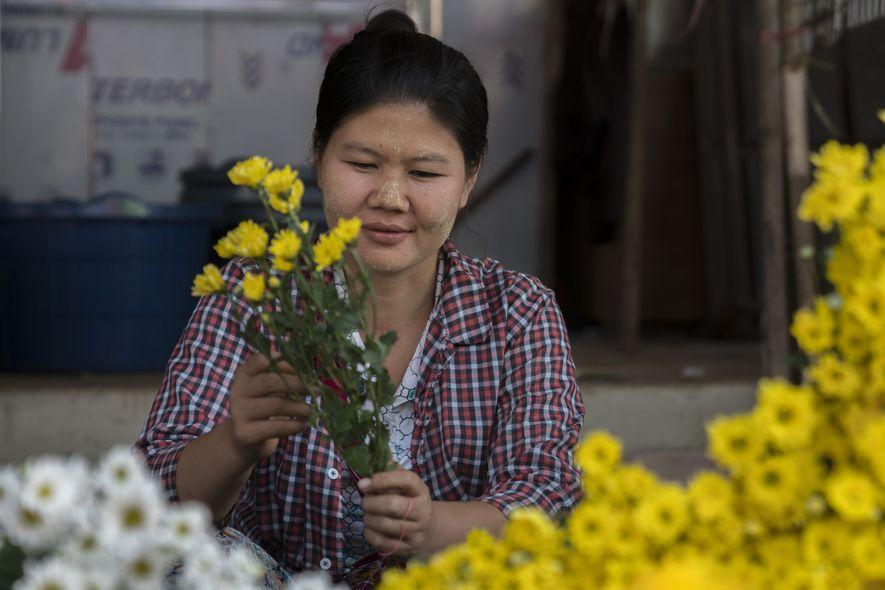 Eine Blumenverkäuferin bindet einen Strauß auf dem traditionellen Markt von Hpa-an.