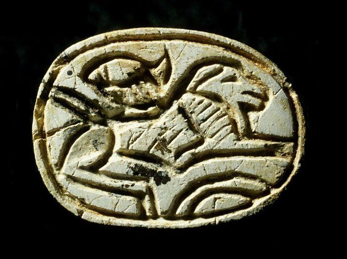 Ein ägyptischer Steinskarabäus, der auf der Brust des Mädchens lag, zeigt einen Löwen und eine aufgehende ...