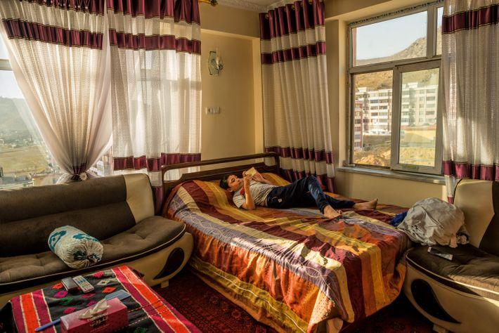 Der zehnjährige Arshid, spielt auf dem Bett seiner Eltern mit dem Smartphone. Drei Generationen teilen sich ...