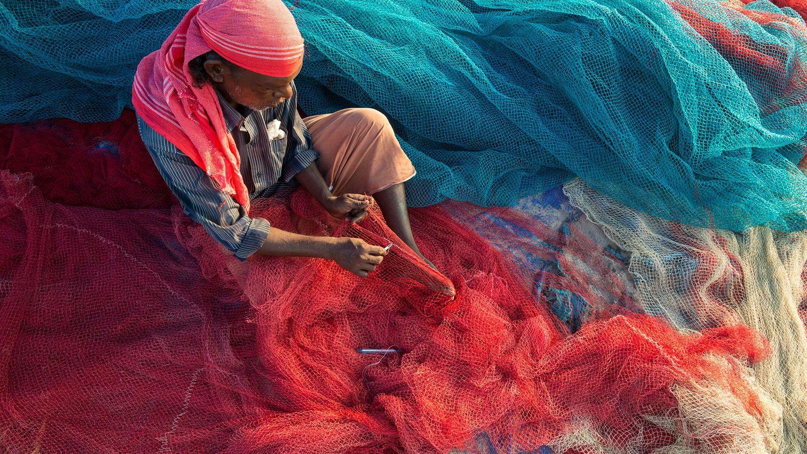 Fischer im indischen Bundesstaat Kerala reparieren ihre Netze. Im Meer schwimmende Plastikteile können die Netze verstopfen ...