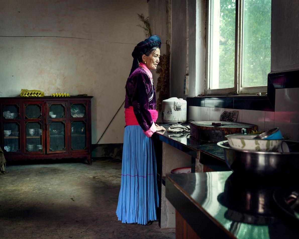Mosuo Frau blickt aus Fenster