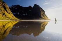 Lauf übers Wasser | An einem abgelegenen Strand auf den Lofoten in Norwegen läuft ein Wanderer ...