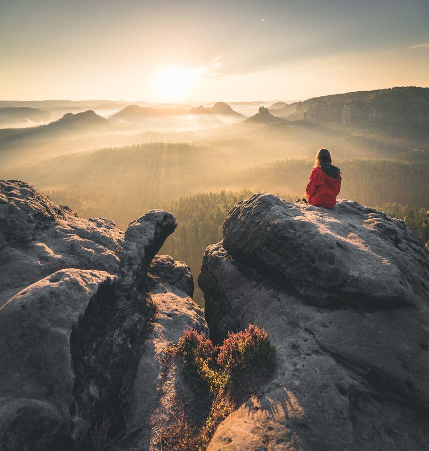 In der Dämmerung taucht die Sonne das neblige Tal in ein goldenes Licht. Die Sächsische Schweiz …