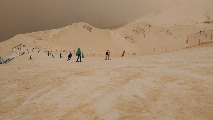 Sand färbt Schnee und Himmel in Europa orange