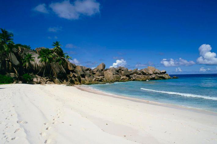 Grand Anse, der längste Strand auf La Digue mit weißem Sand und türkisfarbenem Wasser, ist ein beliebtes Reiseziel.