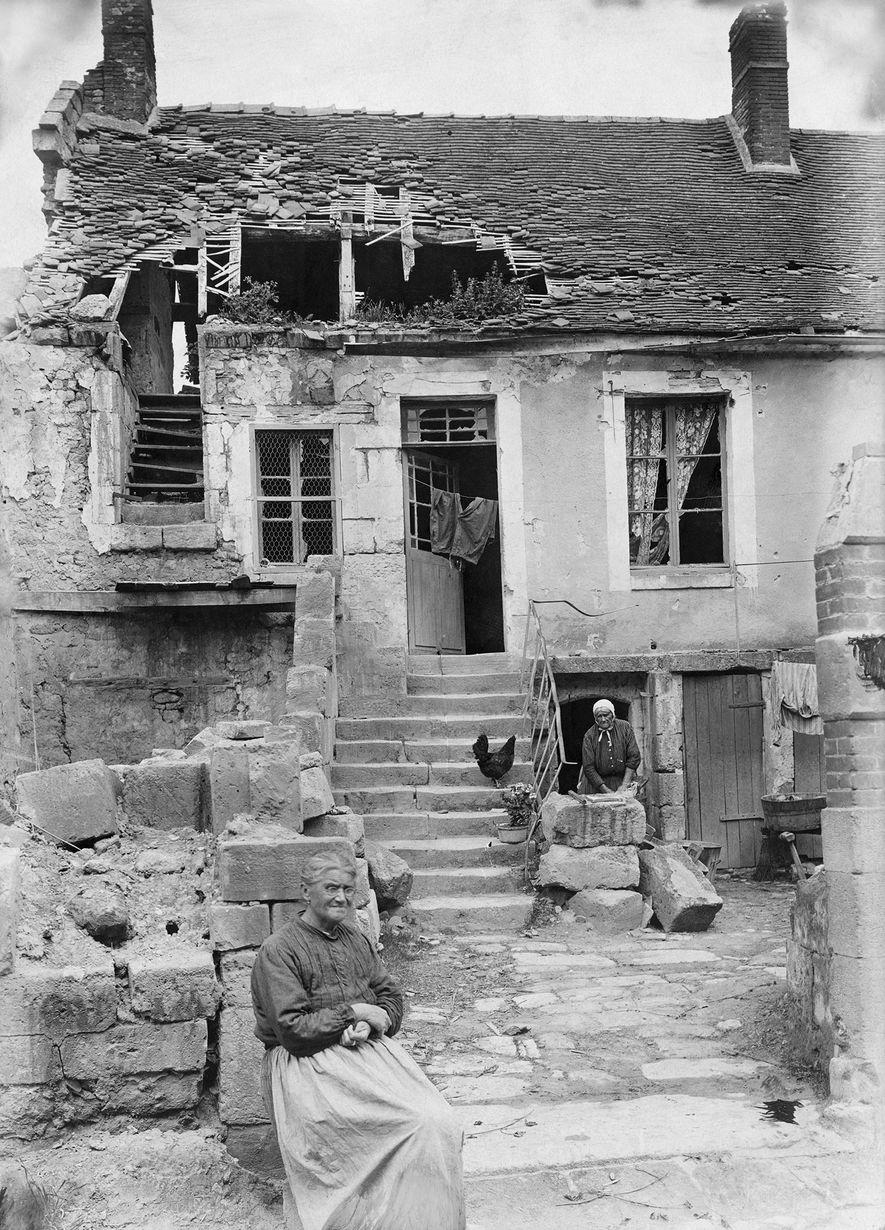 Vor ihren ausgebombten Häusern in Lothringen füllen Frauen Sandsäcke für die Schützengräben. 1917.