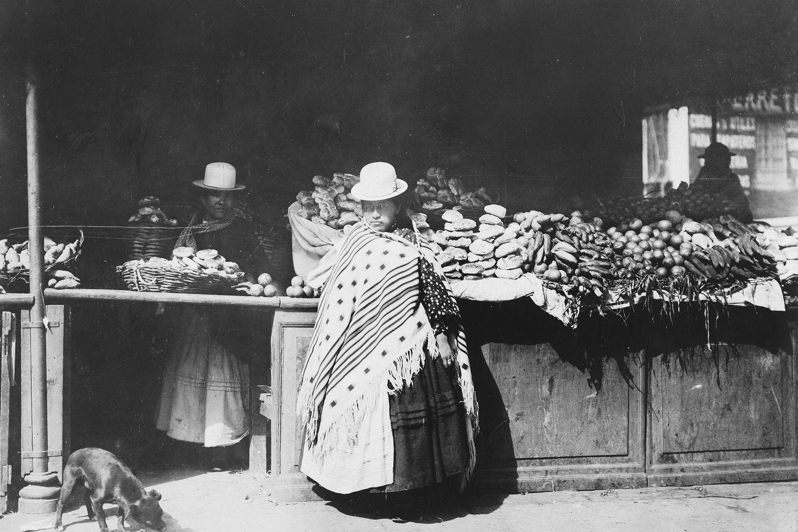 Frauen in traditioneller Kleidung stehen an einem Gemüsestand auf einem Markt in La Paz, Bolivien. 1909.