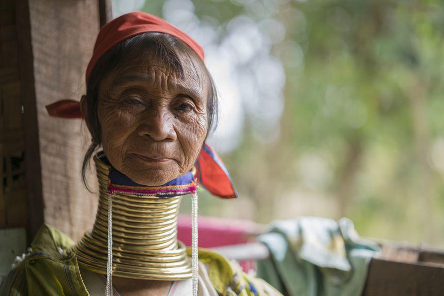 Eine Dame der Padaung, einem Stamm der Karen, auf einer Veranda sitzend. Aufgenommen in der Bergregion ...