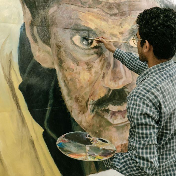 Rao Hassan Nasir aus Karachi malt an einem Gemälde, für das ihm ein Foto eines NCA-Wachmanns, ...