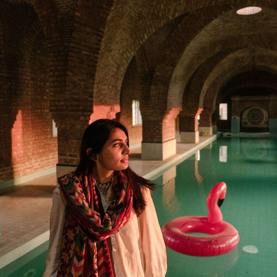 Rabeeya Arif, eine Absolventin des NCA, steht vor dem Schwimmbecken der Künstlerkommune Harsukh in Lahore. Das ...
