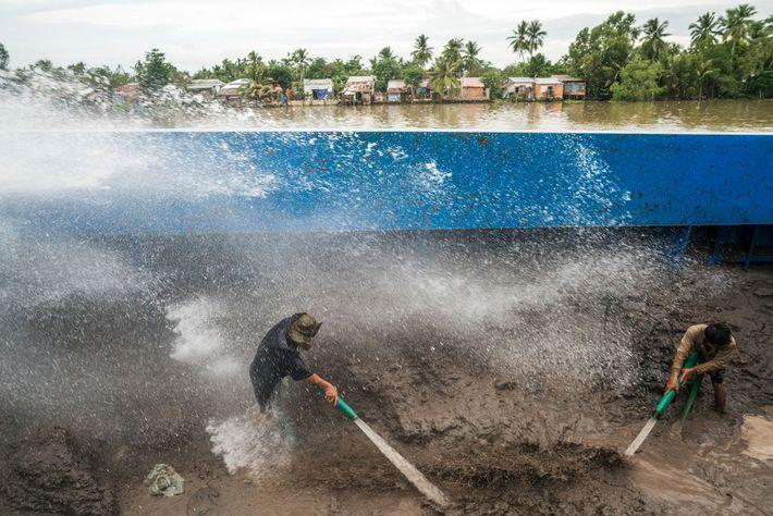 Arbeiter brausen auf einem Lastkahn Sand ab