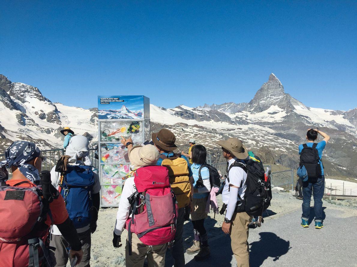 Bergwanderer am Gornergrat vor einem Objektkubus von Branko Šmon.