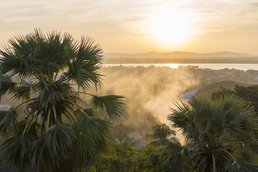 Ein wunderschöner Sonnenuntergang in Mawlamyaing. Die letzten Sonnenstrahlen tauchen die Landschaft und den Nebel nahe des ...