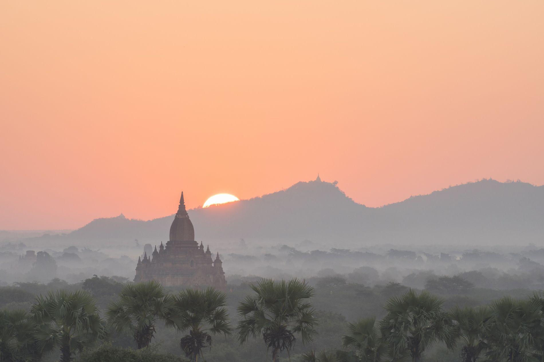 Ein Tempel in Bagan kurz bevor die Sonne über den Horizont tritt und mit ihren Strahlen ...
