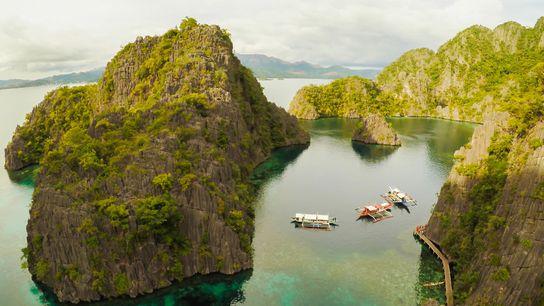 Boote der Tauchschulen dümpeln in der Bucht von Coron, einem der schönsten Tauchreviere der Welt.